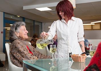Une serveuse sert une vielle femme dans un restaurant.