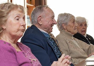 Plusieurs personnes retraitées réunies dans une bibliothèque.