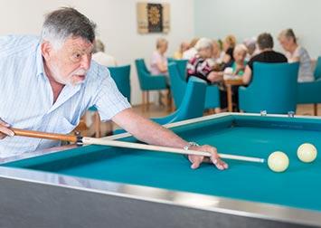 Un retraité joue au billard.