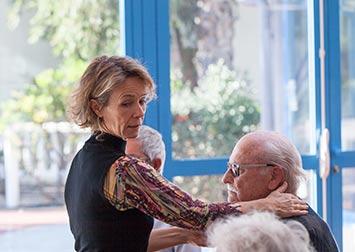 Une femme s'occupe patiemment d'un retraité.