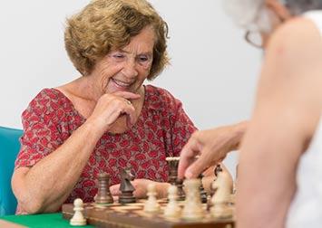 Deux femmes âgées jouent aux échecs et sourient.