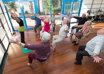 Des retraités suivent les mouvements d'un professeur.