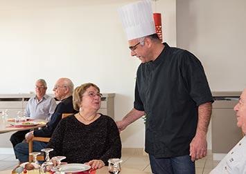 Le chef du restaurant discute chaleureusement avec une retraitée.