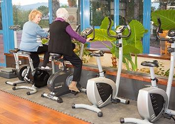 Deux femmes retraitées font du vélo d'appartement dans une salle de sport.