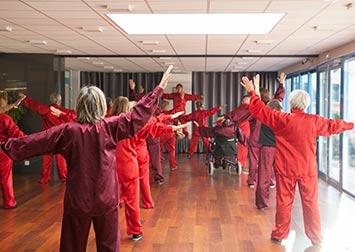 Des retraités vêtus en rouge suivent les mouvements d'un professeur de yoga.